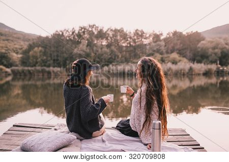 Two Female Friends In Knitted Warm Sweaters Having Picnic Near Lake With Autumn Forest And Lake On T