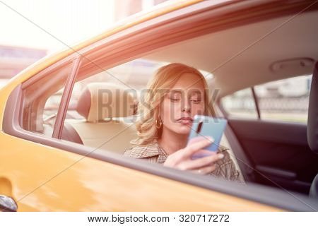 Photo Of Blonde With Phone In Her Hand Sitting In Back Seat In Yellow Taxi In Afternoon. Sunflare Ef