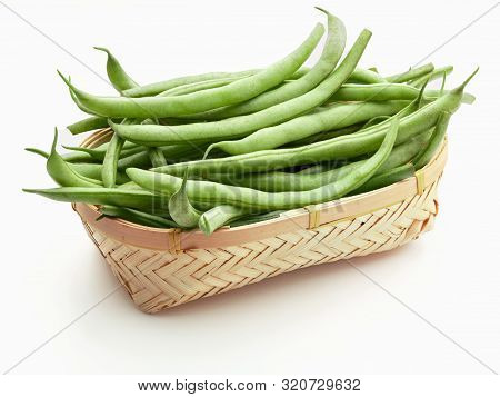 Fresh And Raw Green Beans (green Round Beans) In Wicker Basket. Isolated On White Background