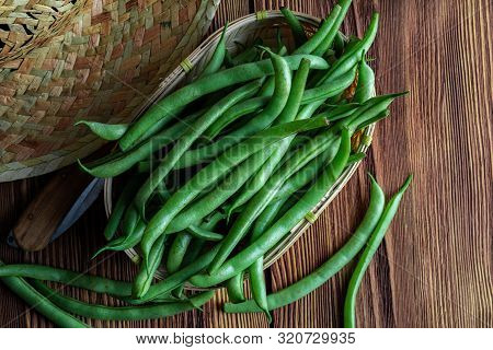 Fresh And Raw Green Beans (green Round Beans) In Wicker Basket. Rustic And Homemade Look On Wooden B