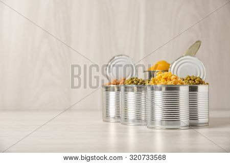 Open Tin Cans With Conserved Vegetables And Fruits On Light Table. Space For Text