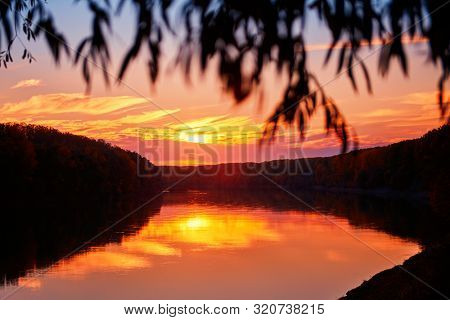 beautiful sunset in autumn season - trees silhouette near a river, bright sunlight
