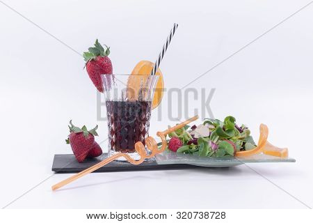 Glass with coca, red strawberries and a slice of ripe orange served with a nutritious tropical salad served on a glass plate, insulated on a white background. Healthy food concept. poster