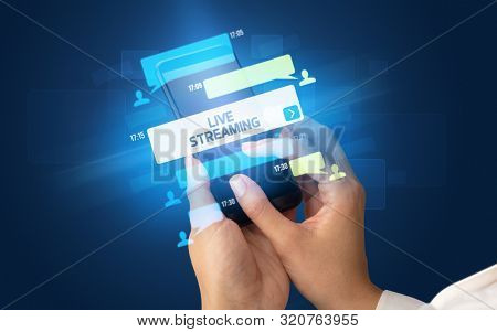 Female hand typing on smartphone with LIVE STREAMING inscription, social networking concept