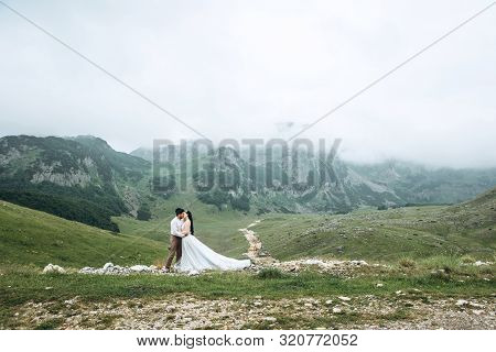 Groom With A Bride Or Couple On A Background Of A Beautiful Mountain Landscape. Wedding In The Highl