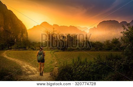 Woman Traveler With Backpack Walks Down The Trail. Limestone Karsts Mountains Vang Vieng Laos
