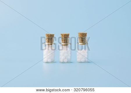 Homeopathic Globules And Glass Bottle On Blue Background. Alternative Homeopathy Medicine Herbs, Hea