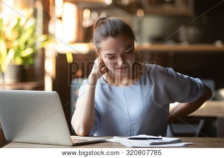 Tired Woman Feeling Pain After Sedentary Computer Work In Cafe