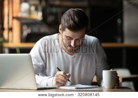 Focused Man Using Laptop And Writing Notes In Coffeehouse