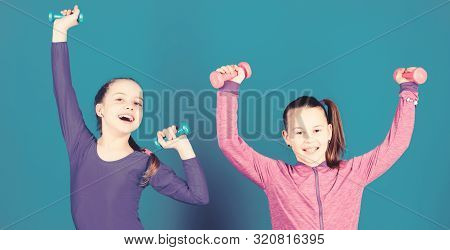 Sport for teens. Easy exercises with dumbbell. Sporty upbringing. On way to stronger body. Girls exercising with dumbbells. Beginner dumbbells exercises. Children hold dumbbells blue background poster