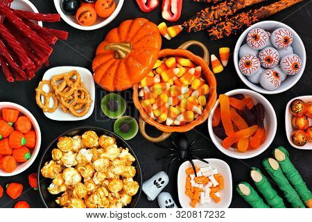 Halloween Candy Buffet Table Scene Over A Black Stone Background. Assortment Of Sweet, Spooky Treats