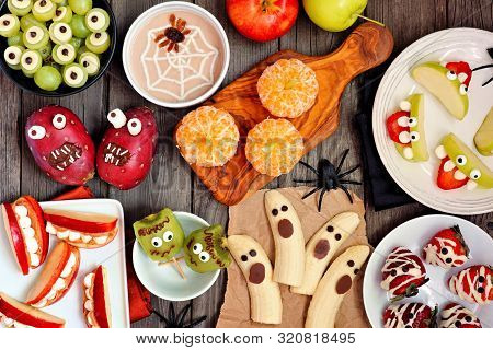 Healthy Halloween Fruit Snacks. Selection Of Fun, Spooky Treats. Top View Table Scene Over A Rustic