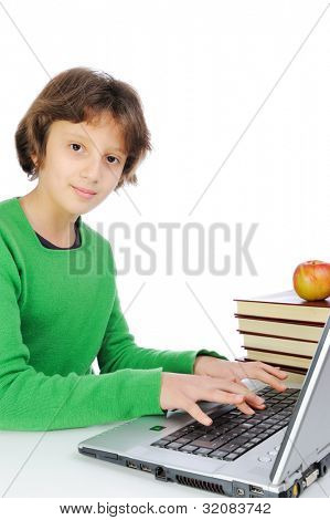 Cute little schoolgirl with laptop and bunch of books in front of her