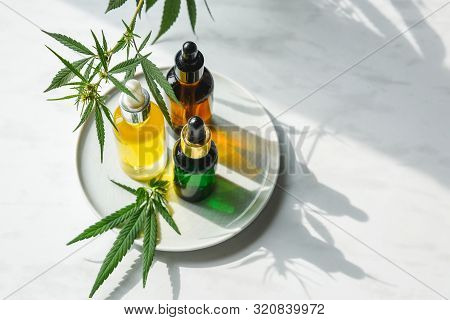 Glass Bottles With Cbd Oil, Thc Tincture And Hemp Leaves On A Marble Background. Flat Lay Cosmetics