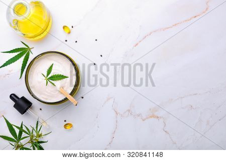 Bank Of Medical Cream With Cbd Oil, Hemp Leaf On A Marble Table. Flat Lay, Top View.