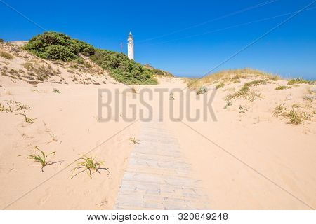 Wooden Planks Footpath Covered On Sand To The Trafalgar Lighthouse