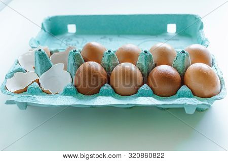 Brown Chicken Eggs And Eggshells in a blue egg box with natural light poster