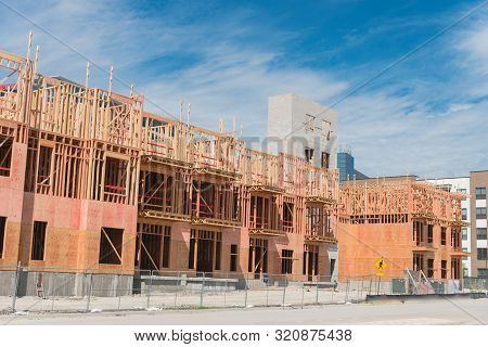 Multistory condominium building under development with elevator shaft and metal fencing near Dallas poster