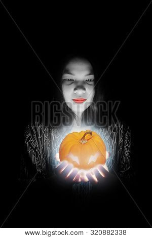 Beautiful Woman Holding Bright Halloween Pumpkin In The Dark Black Background.