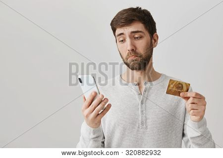 Guy Gets Upset Finding He Has No Money On Bank Account. Gloomy And Sad Man Looks At Screen Of Smartp
