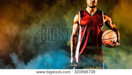 Basketball player against splashing of yellow color powder