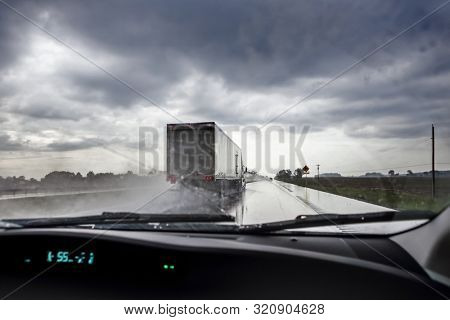 Highway view through the windshield during a rainstorm