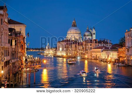 View of Venice Grand Canal with boats and Santa Maria della Salute church in the evening from Ponte dell'Accademia bridge. Venice, Italy