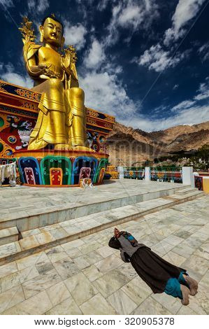 Tibetan Buddhist woman worshiping and praying Buddha Maitreya statue in Likir gompa (monastery), Ladakh, India