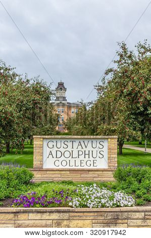 Entrance Sign And Old Main Clock At Gustavus Adolphus College