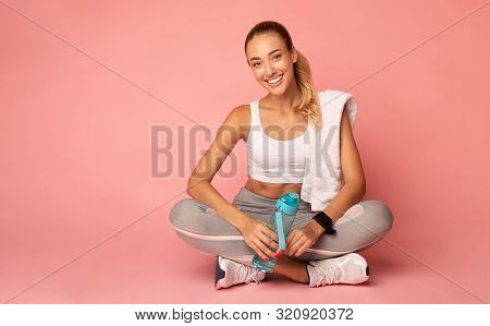 Recovery After Workout Training. Fitness Girl Resting On Floor Holding Water Bottle And Towel On Pin