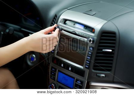 Hand Tunes In Radio Stations And Adjusting Sound Volume On The Car Audio System.