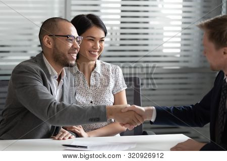 Cheerful Mixed Race Married Spouse Shaking Hands With Real Estate Agent.