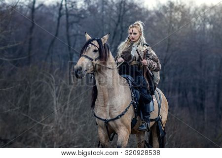 Warrior Viking Blonde Female Riding A Horse In The Woods - Medieval Movie Scene - Focus On The Rider