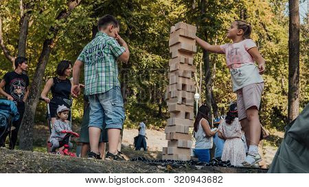 Voronezh, Russia September 5, 2019: Kids Playing In The Park Playing Jenga. Play Jung With A Very La
