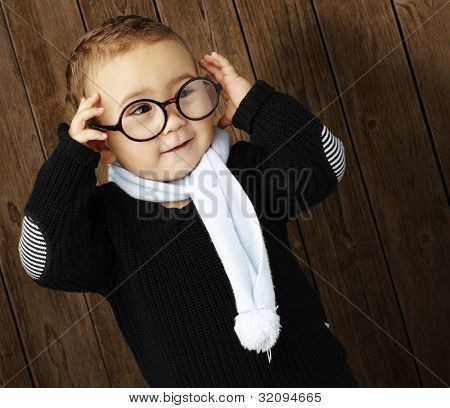 portrait of a funny kid holding his glasses  against a wooden wall