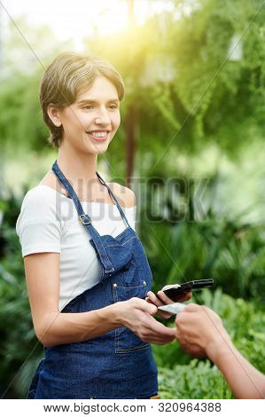Positive Florist In Denim Apron Taking Credit Card From Hand Of Customer To Accept Payment