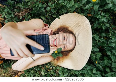 Directly Above View Of Pretty Smiling Girl Enjying Taking Photos When Lying On Green Grass In Park