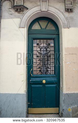 Paris / France - 06 26 2019: Arch Door With Semicircular Top And Door Window Protected By Ornate Met