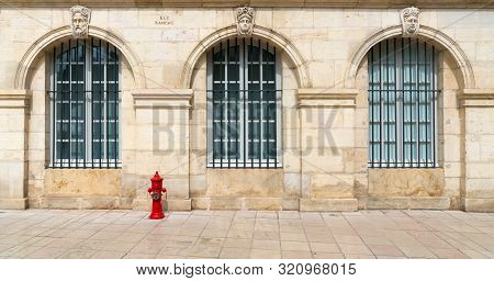 Close Up View Of Stone House Front With Large Grated Windows Of The Art Museum In Dijon With A Red F