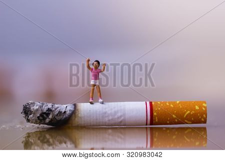Little Kid Standing On The Cigarette. Cigarette And Family Figure. A Concept For Stop Smoking. Smoki