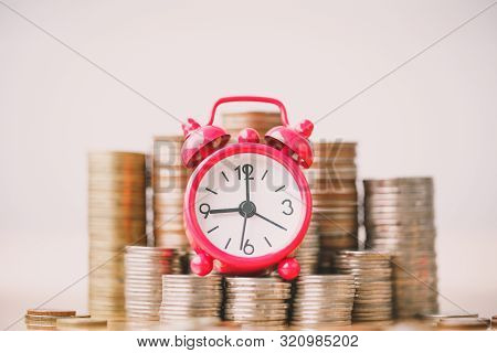 Red Alarm Clock On Stack Of Coins In Concept Of Savings And Money Growing Or Energy Save. Business I