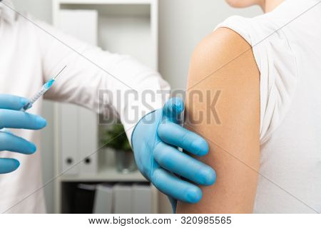 Doctor Giving Patient Vaccine, Flu Shot. Doctor Making A Vaccination In The Shoulder Of Patient