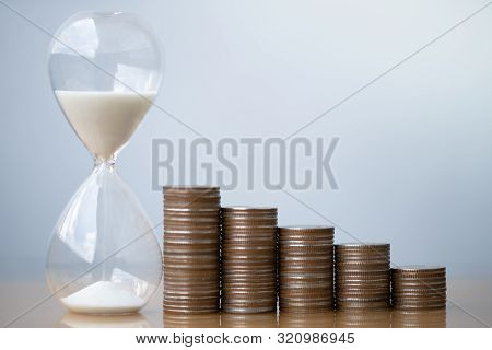 Hourglass White Sand And Stack Of Coins. Business Investment Growth Concept. Money Saving And Invest