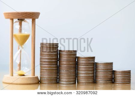 Hourglass Gold Sand And Stack Of Coins. Business Investment Growth Concept. Money Saving And Investm