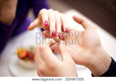 The Guy Takes His Girlfriend S Hand And Puts A Wedding Ring On Her Finger. Marriage Proposal Concept