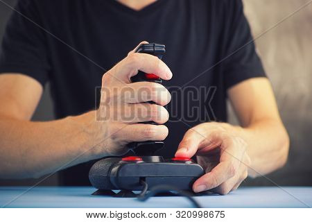 Young Man Playing Video Game With A Retro Joystick. Gaming Joystick From The Mid-1980s. Joystick Has
