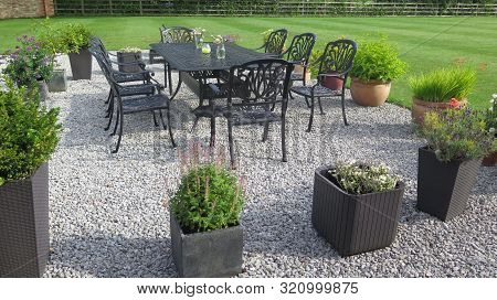 Large Gravel Patioo Area With Table, Chairs And Flower Tubs In Yorkshire Farmhouse Garden, United Ki