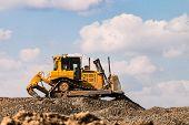 Yellow motorized bulldozer raking rubble piles. Road building industry. poster