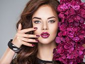 Beautiful  woman with purple make-up of lips and fingernails. Closeup woman's portrait with flowers. Young caucasian gorgeous attractive girl . Model. Vivid make-up. Sexy female. Violet fingernails poster