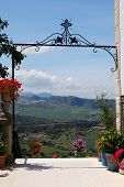 RONDA, SPAIN - MAY 13, 2008 - Ornate iron gateway at Don Bosco house with views across the countryside towards the mountains, Ronda, Malaga Province, Andalucia, Spain, Europe, May 13, 2008. poster